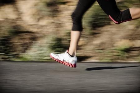 mujeres corriendo: acci�n de desenfoque de movimiento pies corriendo por la carretera, de buena condici�n f�sica el entrenamiento de velocidad Foto de archivo