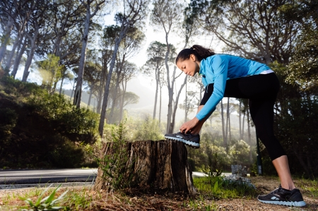 runner tying her shoelace while preparing for fitnes training outdoors in the forest with morning sinlight photo