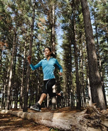 trail running: trail running jump fitness woman training alone outdoors in the forest