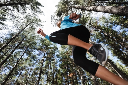 jungle girl: trail running jump fitness woman training alone outdoors in the forest