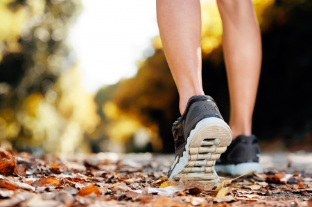 close up: close up of feet of a runner running in autum leaves training for marathon and fitness healthty lifestyle