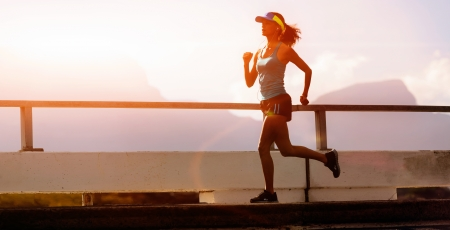 runner silhouette: runner training at sunset, silhouette of fitness marathon woman with lens flare and action