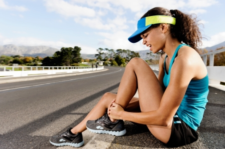 strained: Runner with ankle injusry has sprained and strained ankle, painful expression. typical road running problem associated with shoe choice