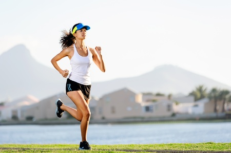 Fitness woman running in a suburb at sunset, healthy wellness workout exercise  athlete. photo