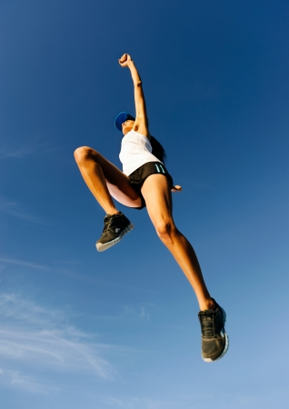 endurance: Athlete celebrating jumping and leaping against a blue sky. healthy wellness fitness woman in air Stock Photo