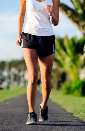 Runner jogging along a pathway in a park outdoors healthy wellness fitness athlete training photo
