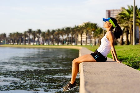 healthy woman relaxing after exercise sitting near the water in an urban park space photo
