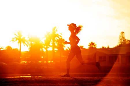Runner running in a suburb, healthy fitness wellness vitality athlete silhouetted against the sun flare photo