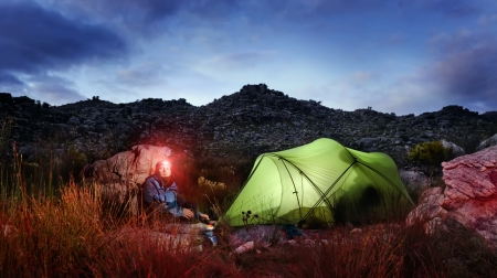 camping equipment: Tent camping wilderness adventure man with headlamp and gas burner in the mountains cooking food at night while looking into panorama of the great outdoors