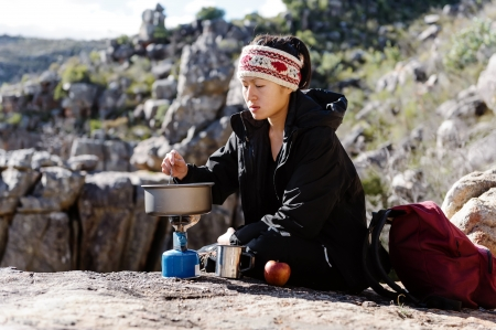 Portrait of an asian chinese backpacker cooking on a camping gas stove while hiking and exploring on a tourist adventure in the wilderness mountains photo