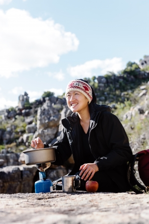 Portrait of an asian chinese backpacker cooking on a camping gas stove while hiking and exploring on a tourist adventure in the wilderness mountains Stock Photo - 14053805