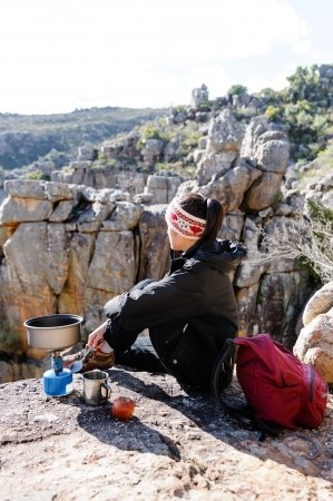 Chinese asian woman sitting and enjoying the view after a hike, trek in the mountains on an adventure tourism holiday camping trip photo