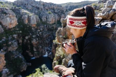 Portret azjatyckich turysty chiński miecha i picia kubek kawy podczas wędrówek i odkrywania na przygody turystycznej w górach pustyni