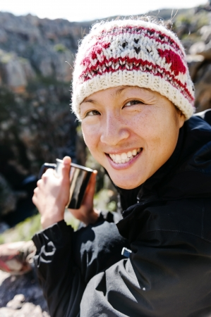 Portrait of an asian chinese backpacker smiling and drinking a mug of coffee while hiking and exploring on a tourist adventure in the wilderness mountains photo