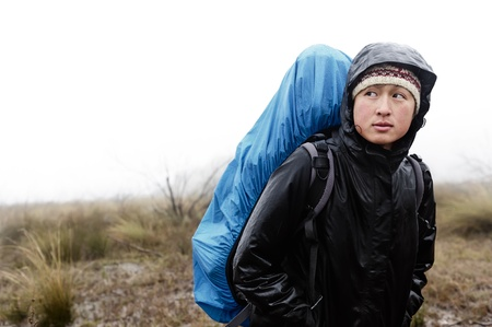 girl in rain: portrait of asian hiker with waterproof gear and backpack in the rain while trekking on an adventure expedition in the mountains during bad weather, cold and miserable
