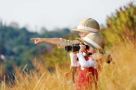 brother and sister: Happy young safari adventure children playing outdoors in the grass with binoculars and exploring together as brother and sister.