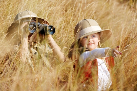 kid pointing: Happy young safari adventure children playing outdoors in the grass with binoculars and exploring together as brother and sister.