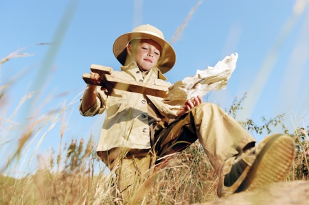 Adventure explorer treasure map boy with wooden sword plays outdoors in a field having fun photo