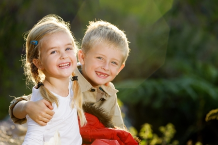 sister: Portrait of adorable brother and sister smile and laugh together while sitting outdoors. happy lifestyle kids