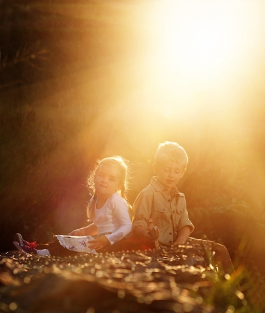 playing field: Portrait of two young children sitting together in the sunlight outdoors. brother and sister siblings