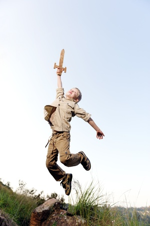 Young boy jumping with wooden sword playing an adventure exploring game outside  photo