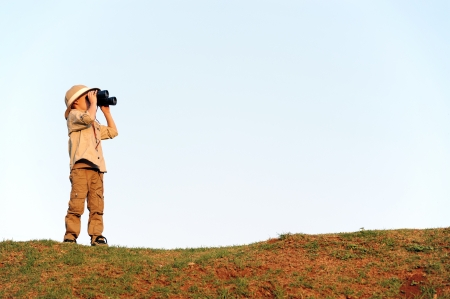 explorer: Young explorer looking with binoculars in safari clothing.  Stock Photo