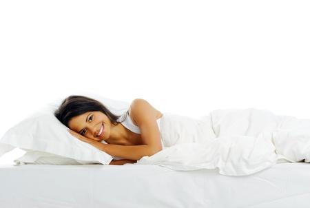 white linen: Retrato de una mujer linda en la cama sonriendo con una cara feliz y pac�fica de lino blanco Foto de archivo
