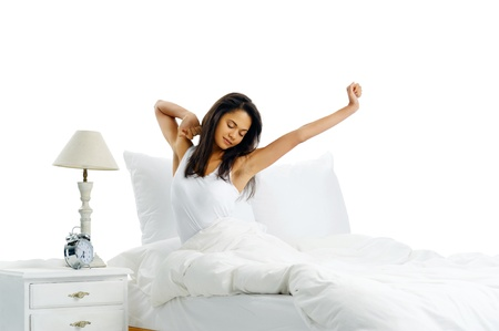 up wake: yawn stretch sleepy latino woman in bed waking up to the sound of her alarm clock isolated on white background
