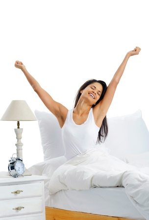 waking: Joy cheerful happy woman waking up with a smile in bed and stretching her arms up Stock Photo