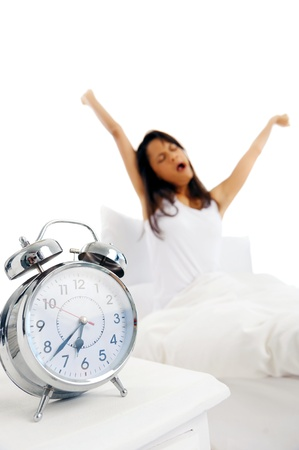 early morning: Alarm clock ringing with time to wake up, woman stretching and yawning in the background  focus on alarm clock   Stock Photo