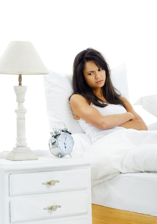 Unhappy woman awake from alarm clock early in the morning is upset about getting out of bed photo