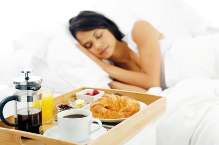 Breakfast in bed for sleeping latino woman  dreaming of a healthy coffee croissant and yogurt meal  photo