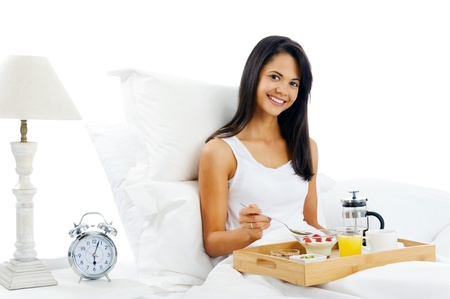 adult indian: Portrait of happy latino woman eating breakfast in bed, smiling and healthy