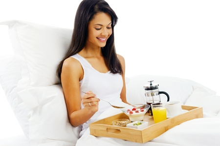 bed and breakfast: Portrait of happy latino woman eating breakfast in bed, smiling and healthy