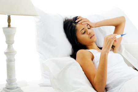 ragazza malata: Donna malata a letto con termometro e il viso febbre infelice isolato su sfondo bianco