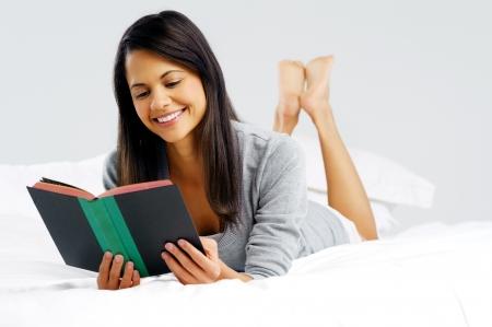 mujer leyendo libro: Mujer leyendo un libro en la cama, acostado boca abajo sonriendo feliz y relajada en un d�a de ocio en el hogar Foto de archivo