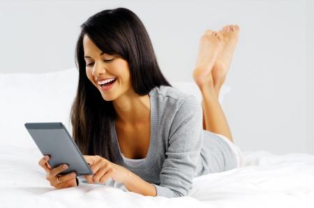 mujer en la cama: mujer que lee un dispositivo Tablet PC moderna mientras se está acostado en la cama feliz y sonriente