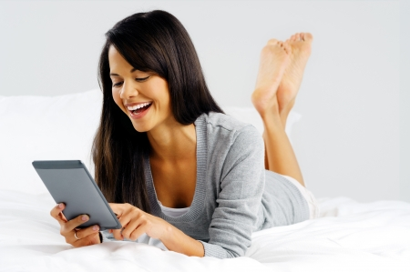 woman reading: woman reading a modern computer tablet device while lying in bed happy and smiling