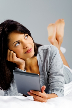 woman reading a modern computer tablet device while lying in bed thinking and wondering to herself photo