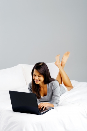 Young attractive latino woman using laptop computer while lying on bed in casual clothes photo