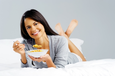 Happy woman with bowl of cornflakes eating breakfast in bed  healthy start to the day photo
