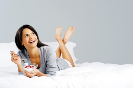 Portrait of a happy smiling latino hispanic woman eating a healthy breakfast of fruit and yoghurt in bed   Stock Photo - 14181992
