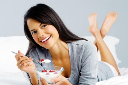 yogur: Retrato de un feliz y sonriente mujer latina hispana de comer un desayuno saludable de fruta y el yogur en la cama