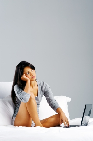 Portrait of attractive young woman in bed with laptop thinking and sitting  photo
