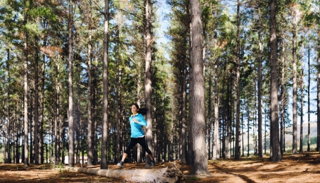 Woman trail running in the woods and jumping over logs while on extreme outdoor fitness training in forest.  photo