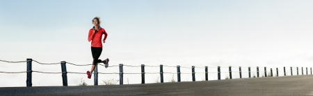 a panorama: Athletic runner training alone on a road outdoors for marathon and fitness. healthy wellness exercise panorama with copyspace.
