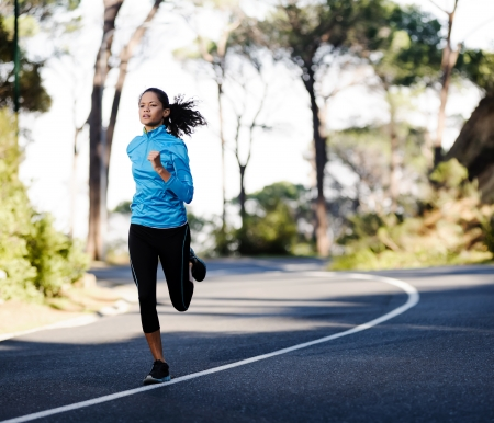 perseverance: Fitness athlete training alone on a mountain road. Running endurance marathon woman exercising for healthy lifestyle and wellness. panorama with copyspace