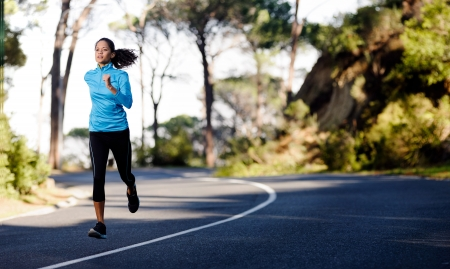 Fitness athlete training alone on a mountain road. Running endurance marathon woman exercising for healthy lifestyle and wellness. panorama with copyspace photo