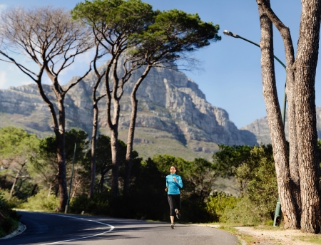 willpower: Fitness athlete training alone on a mountain road. Running endurance marathon woman exercising for healthy lifestyle and wellness. panorama with copyspace XXL Stock Photo