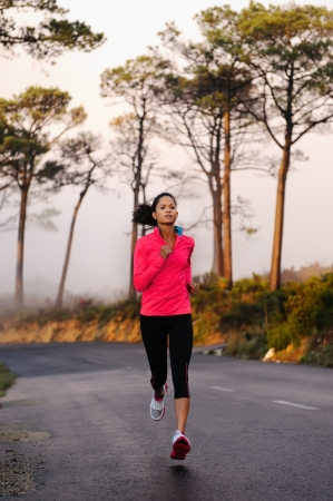 Running on the road in the misty morning  woman athlete training photo
